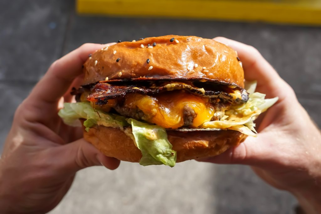 A pair of hands holding a cheese burger