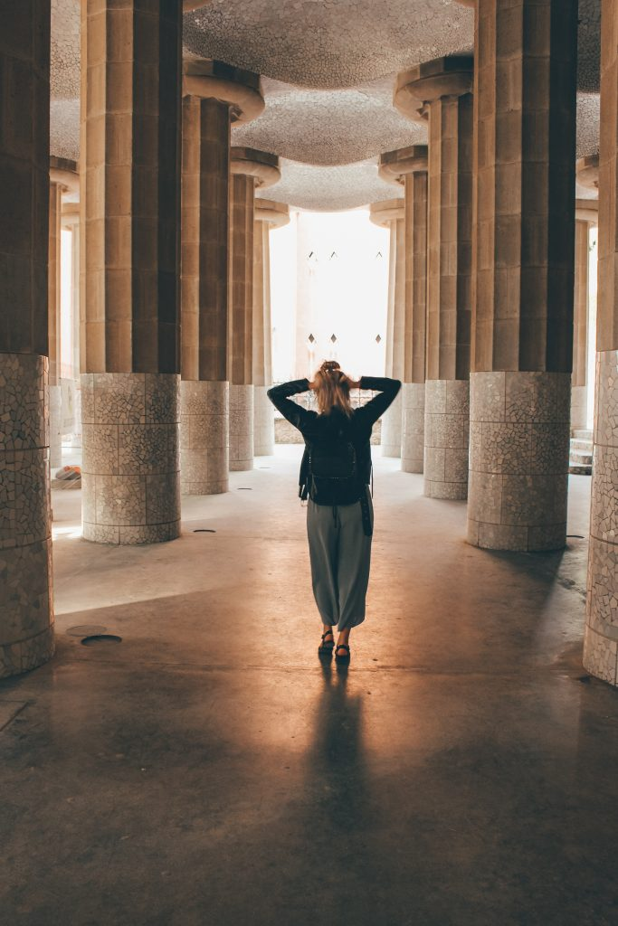 Woman standing in a corridor between pillars