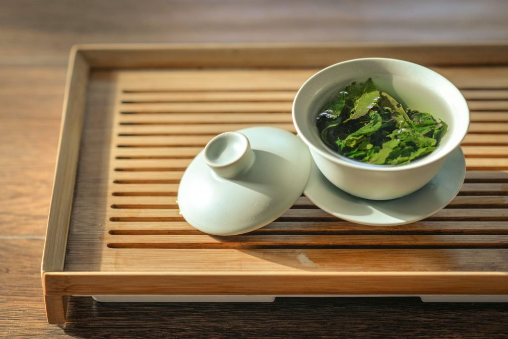 green tea leaves in white ceramic bowl with open lid: may help your body build reserves to cope with fever.