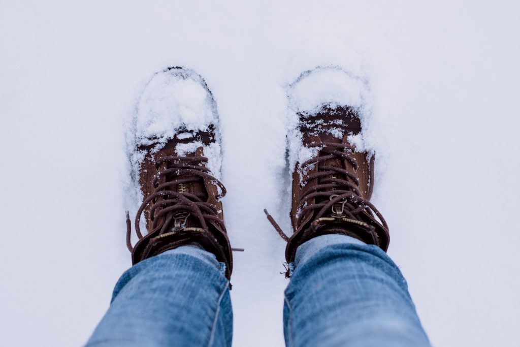 person wearing brown leather boots converted by snow