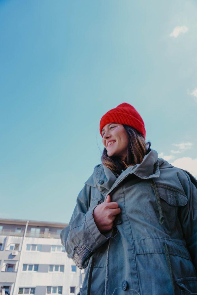 mulher de jaqueta cinza e boné de malha vermelha: roupas quentes para deficiência de Yang do coração