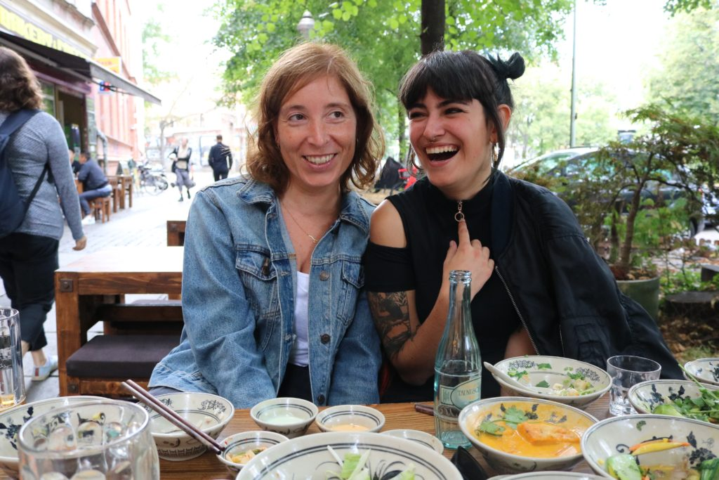 two women sitting on bench at table: eat with people you like and laugh with to help reduce Heart Fire!